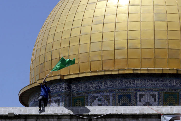 A man waves the Hamas flag during a protest against the likely evictions of Palestinian families from the homes, after the last Friday prayers of the Muslim holy month of Ramadan at the Dome of the Rock Mosque in the Al Aqsa Mosque compound in the Old City of Jerusalem, Jerusalem, Friday, May 7, 2021. (AP Photo/Mahmoud Illean)