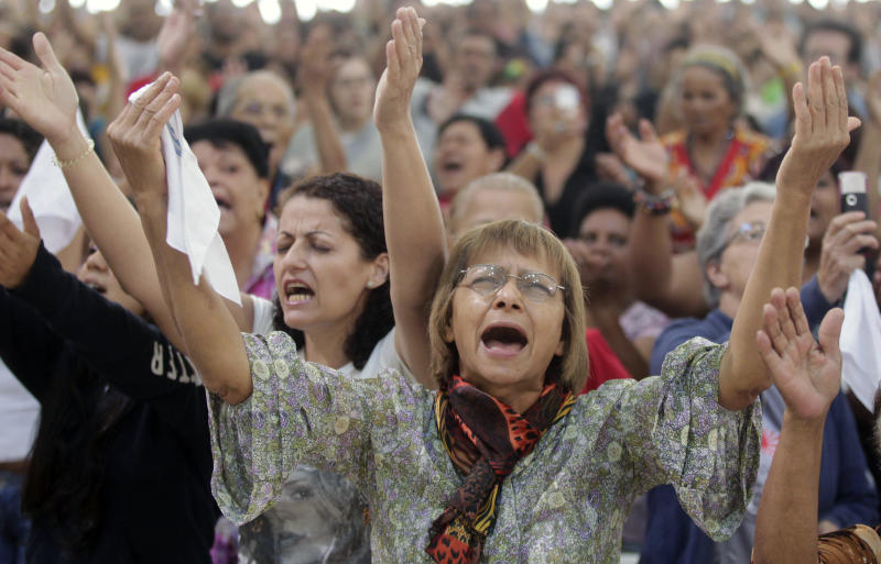 People attend a Mass led by Catholic priest Marcelo Rossi at the Mother of God sanctuary in Sao Paulo, Brazil, Saturday, Nov. 3, 2012.   Rossi, a Latin Grammy-nominated Christian music singer and author of best-selling books in Brazil, inaugurated on Friday the massive new Roman Catholic church that will hold about 20,000 worshippers when complete. (AP Photo/Andre Penner)