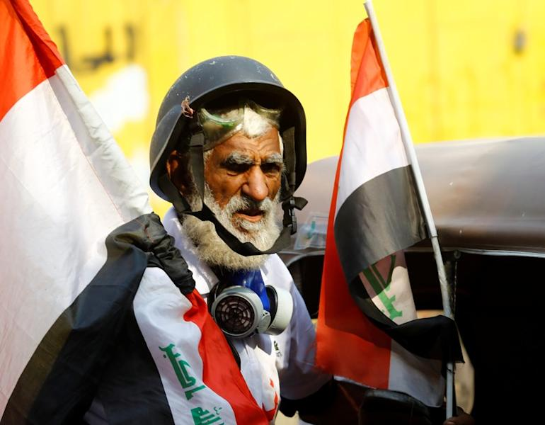 Demonstrator holds the Iraqi flag during the ongoing anti-government protests in Baghdad