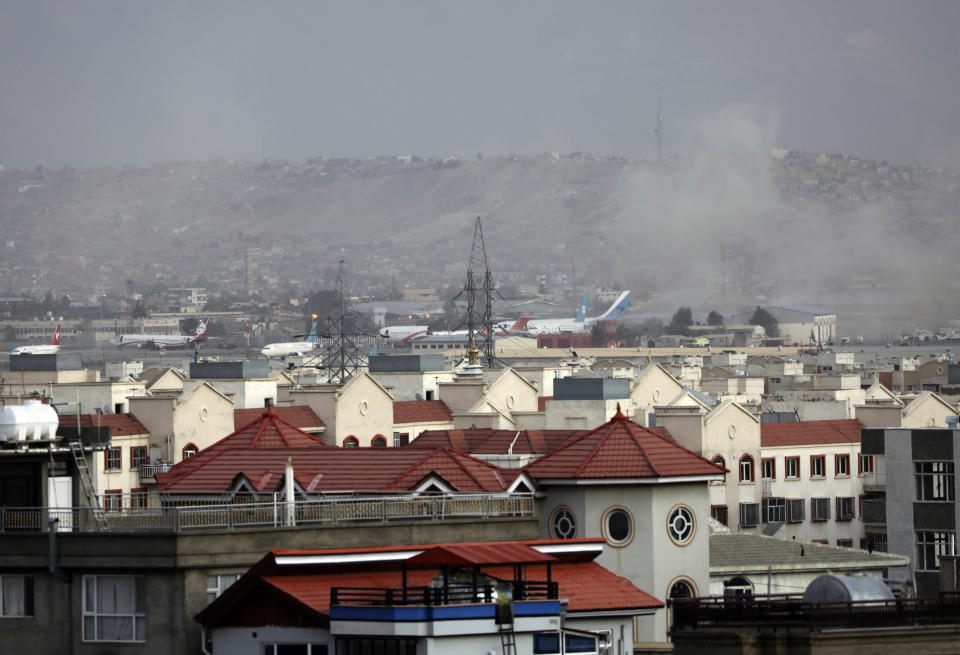 Smoke rises from a deadly explosion outside the airport in Kabul, Afghanistan, Thursday, Aug. 26, 2021. Two suicide bombers and gunmen have targeted crowds massing near the Kabul airport, in the waning days of a massive airlift that has drawn thousands of people seeking to flee the Taliban takeover of Afghanistan. (AP Photo/Wali Sabawoon)