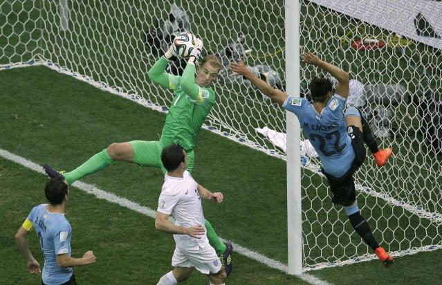 England's goalkeeper Joe Hart makes a save ahead of Uruguay's Martin Caceres, right, during the group D World Cup soccer match between Uruguay and England at the Itaquerao Stadium in Sao Paulo, Brazil, Thursday, June 19, 2014. (AP Photo/Michael Sohn)