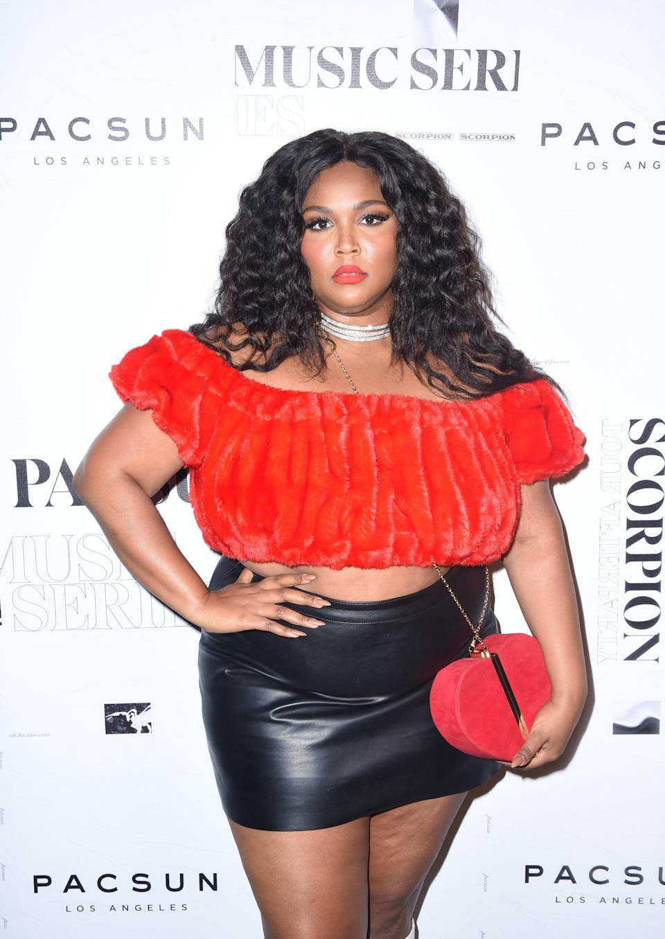Lizzo opted for a red off-the-shoulder top, black leather skirt, and a matching heart-shaped purse for a night out.