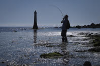 A man is silhouetted in the morning light as he fishes in the Teign estuary in Shaldon, Devon, England, Sunday July 18, 2021. Visiting the fishing village of Shaldon a small cluster of mainly Georgian houses and shops at the mouth of the River Teign, is like stepping back into a bygone era. It features simple pleasures that hark back to analog, unplugged summer days: a book and a picnic blanket, a bucket and spade, fish and chips.(AP Photo/Tony Hicks)