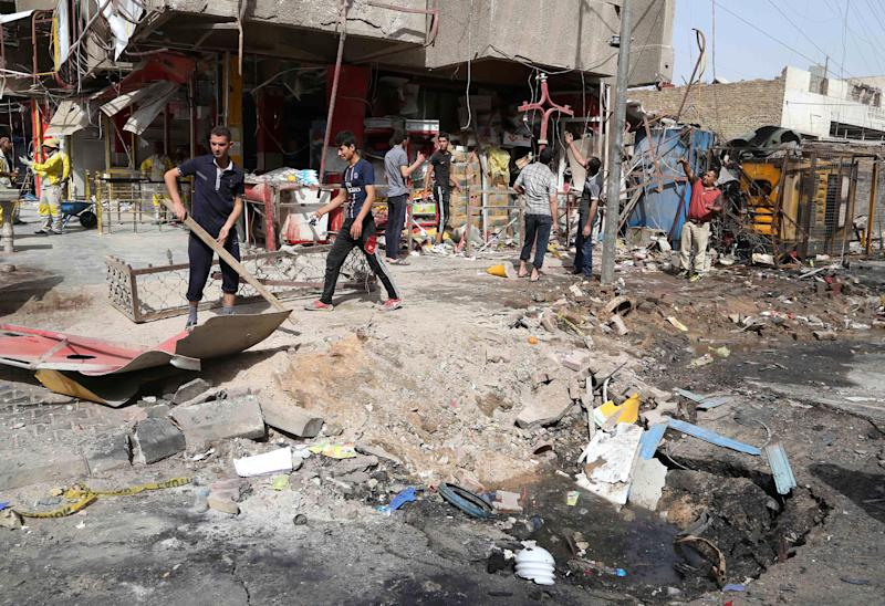 Iraqis sift through the aftermath of a car bomb attack in the crowded commercial area of Karrada, in Baghdad, Iraq, Friday, April 18, 2014. Authorities in Iraq say a car bomb targeted a street full of shoppers in the capital. in Baghdad on Thursday.(AP Photo/Karim Kadim)