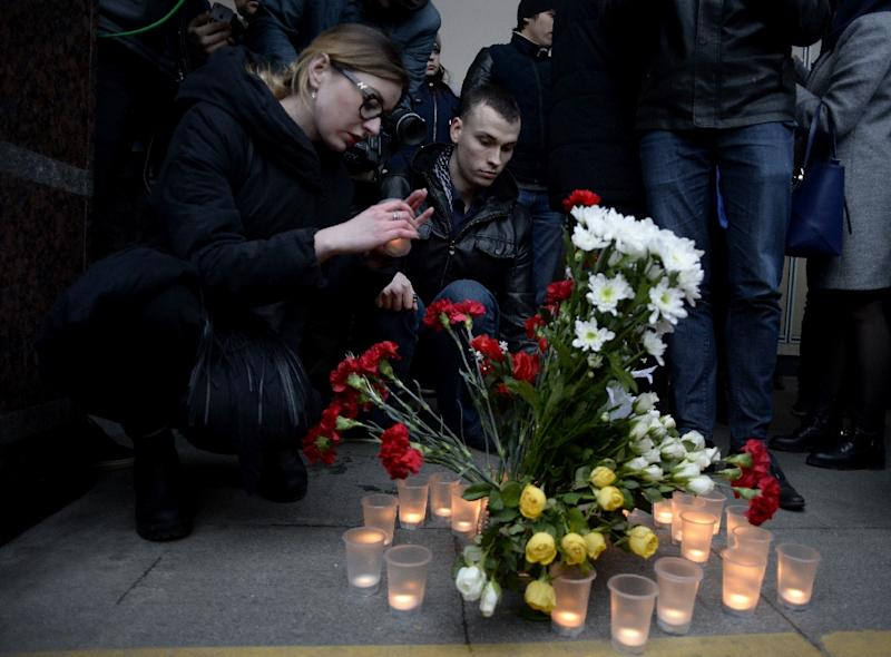 People place flowers and lit candles in memory of victims of the blast in the Saint Petersburg metro outside Sennaya Square station on April 3, 2017 (AFP Photo/Olga MALTSEVA)