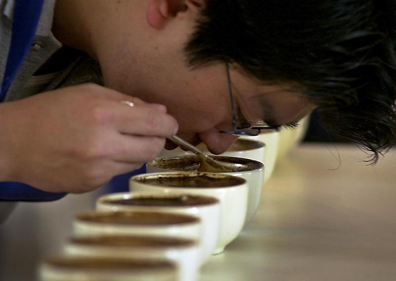 FILE - In this Wednesday, April 30, 2003 file photo, Yoshi Kato tests coffee for aroma, texture and taste during a contest of Nicaraguan coffee growers in Managua, Nicaragua. A large U.S. federal study concludes people who drink coffee seem to live a little longer. Researchers saw a clear connection between cups consumed and years of life. Whether it was regular or decaf didn't matter. The results are published in the Thursday, May 17, 2012 New England Journal of Medicine. (AP Photo/Esteban Felix)