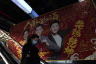 A woman wearing a mask passes by an ad for a movie in Beijing Thursday, Feb. 25, 2021. The state of the world's second largest economy takes precedence among the myriad issues presented by Premier Li Keqiang in his address at the National People's Congress opening session to take place on Friday, March 5. 2021. (AP Photo/Ng Han Guan)