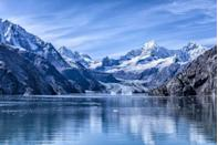 <p>Glacier Bay National Park is just west of Juneau in Alaska, and it's a national monument and UNESCO World Heritage Site. The snow-capped mountains stand out against the blue sky on a cold winter's day.</p>