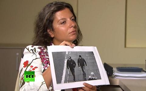 RT Editor-in-Chief Margarita Simonyan shows an image of two men during an interview with Alexander Petrov and Ruslan Boshirov - Credit: TASS via Getty Images