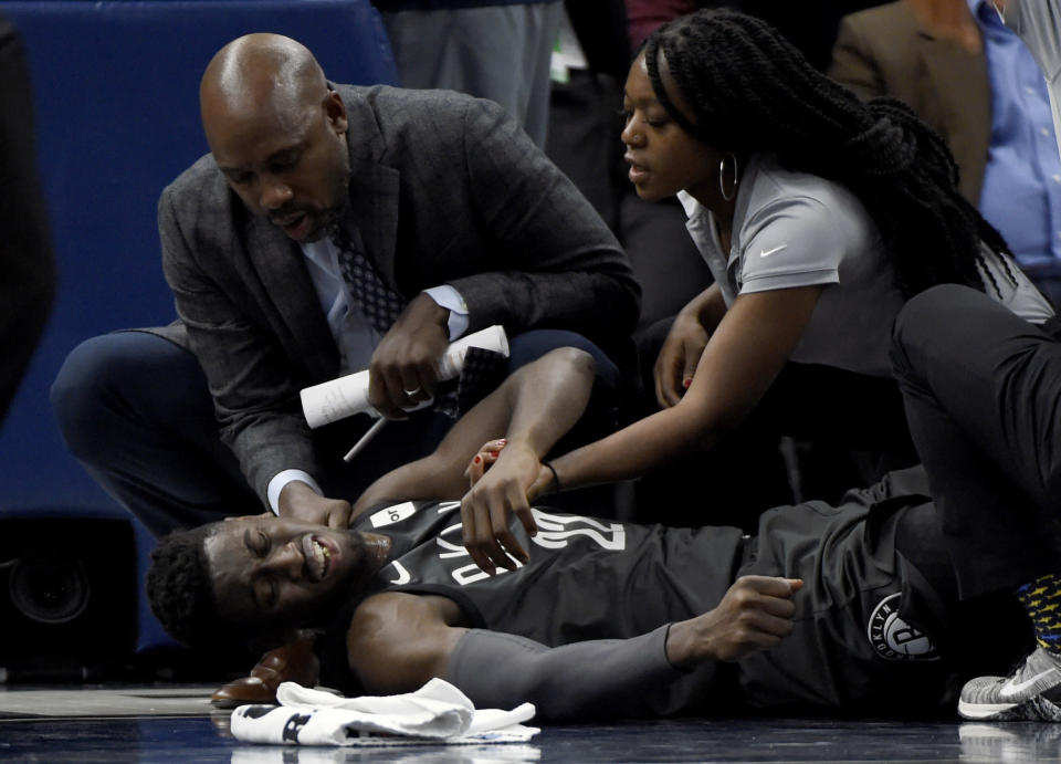 Brooklyn Nets guard Caris LeVert (22) is tended to after an injury during the second quarter of an NBA basketball game against the Minnesota Timberwolves on Monday, Nov. 12, 2018, in Minneapolis. (AP Photo/Hannah Foslien)