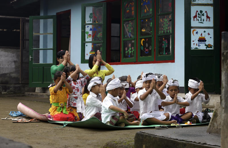 Kindergarten children pray for Mount Agung volcano in their school in Karangasem, Bali, Indonesia, Thursday, Oct. 5, 2017. More than 140,000 people have fled from the surrounds of Mount Agung since authorities raised the volcano's alert status to the highest level on Sept. 22 after a sudden increase in tremors. It last erupted in 1963, killing more than 1,000 people. (AP Photo/Firdia Lisnawati)