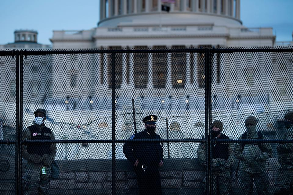 TOPSHOT - A Capitol Police officer stands with members of the National Guard behind a crowd control fence surrounding Capitol Hill a day after a pro-Trump mob broke into the US Capitol on January 7, 2021, in Washington, DC. (Photo by Brendan Smialowski / AFP) (Photo by BRENDAN SMIALOWSKI/AFP via Getty Images) (Photo: AFP via Getty Images)