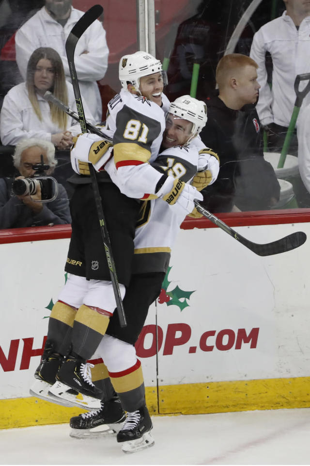 Vegas Golden Knights right wing Reilly Smith (19) lifts center Jonathan Marchessault (81) in the air after Marchessault scored his third goal of the night during the third period of an NHL hockey game against the New Jersey Devils, Tuesday, Dec. 3, 2019, in Newark, N.J. The Golden Knights defeated the Devils 4-3. (AP Photo/Kathy Willens)