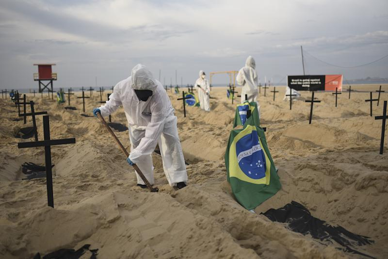 RIO DE JANEIRO, BRAZIL â JUNE 11 : Protesters, wearing protective gear, dig mock graves on Copacabana beach symbolizing deaths due to the coronavirus (COVID-19) and protest against governments actions towards the pandemic, in Rio de Janeiro, Brazil on June 11, 2020. Act calls for transparency and attitude change from the government to fight the virus. The novel coronavirus continued to spread throughout Latin America on Thursday, with the death toll climbing to over 72,000. The region is currently considered the epicenter of the health crisis and accounts for nearly half of the deaths and cases worldwide. Residents of Rio de Janeiro woke up Thursday to see 100 open graves at the city's most emblematic beach. During the night, Brazilians critical of President Jair Bolsonaroâs response to the coronavirus pandemic dug 100 graves and stuck black crosses in the sand of Copacabana beach in a tribute to the nearly 40,000 people who have died so far in Brazil from COVID-19. (Photo by Fabio Alarico Teixeira/Anadolu Agency via Getty Images)