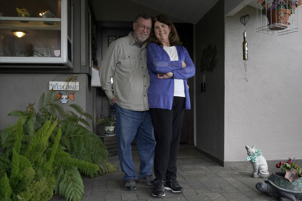 """John and Laurie Miller pose outside of their home in San Jose, Calif., Wednesday, March 10, 2021. The Millers were passengers on the Grand Princess cruise ship, which had captured the world's attention in 2020 when it became clear the coronavirus pandemic had arrived at U.S. shores on board the boat. """"There was so much inconsistent information from day-to-day that it felt like we were guinea pigs,"""" Laurie Miller said. (AP Photo/Jeff Chiu)"""