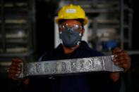 A worker shows an ingot made from lead at ACE Green recycling Inc in Ghaziabad