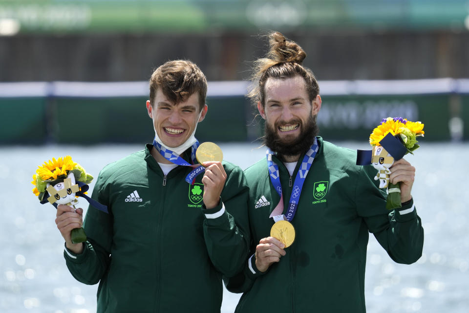 Gold medalists Fintan Mc Carthy and Paul O'Donovan of Ireland celebrate during the medal ceremony for the lightweight men's rowing double sculls final at the 2020 Summer Olympics, Thursday, July 29, 2021, in Tokyo, Japan. (AP Photo/Lee Jin-man)