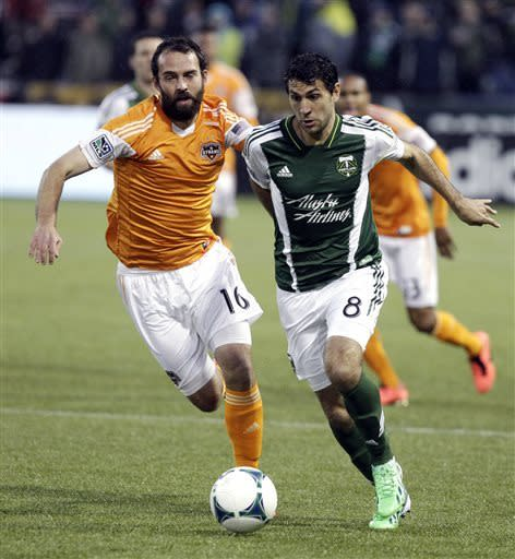 Portland Timbers midfielder Diego Valeri, right, and Houston Dynamo midfielder Adam Moffat chase down the ball during the first half of an MLS soccer game in Portland, Ore., Saturday, April 6, 2013. (AP Photo/Don Ryan)