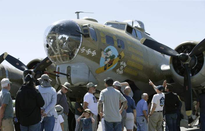 "In this photo taken June 2, 2018 photo, people look over the Nine-O-Nine, a Collings Foundation B-17 Flying Fortress, at McClellan Airport in Sacramento, Calif. A B-17 vintage World War II-era bomber plane crashed Wednesday, Oct. 2, 2019, just outside New England's second-busiest airport, and a fire-and-rescue operation was underway, official said. Airport officials said the plane was associated with the Collings Foundation, an educational group that brought its ""Wings of Freedom"" vintage aircraft display to Bradley International Airport this week in Windsor Locks, Conn. (AP Photo/Rich Pedroncelli)"