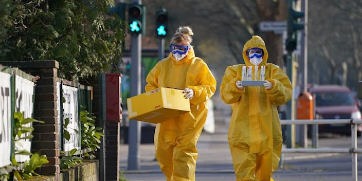 BERLIN, GERMANY - MARCH 27: Medical volunteers dressed in protective suits, masks, gloves and goggles return to a medical practice after taking blood and throat mucous samples from visitors to test them for Covid-19 infection at a tent set up next door on March 27, 2020 in Berlin, Germany. Doctor Ulrike Lipke said she set up the tent as a way to offer testing yet avoid possible coronavirus infection inside the premises of her practice. Germany is seeking to radically ramp up its coronavirus testing capacity to up to 200,000 tests per day by the end of April as a means to allow people to return to work and hence get the crisis-stricken German economy back into gear. (Photo by Sean Gallup/Getty Images)