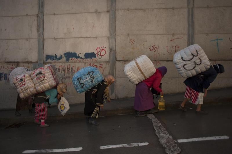 Women porters carry bundles on their backs for transport across the El Tarajal boarder separating Morocco and Spain's North African enclave of Ceuta, in Ceuta on December 4, 2014 (AFP Photo/Jorge Guerrero)