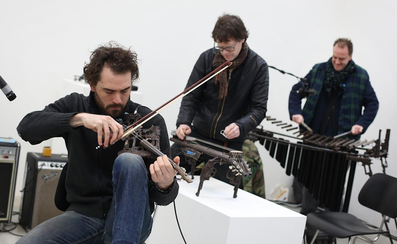 LONDON, ENGLAND - MARCH 26:  (L-R) Tom Lamb, John Coxon and Charles Hayward perform on musical instruments made from recycled gun parts,  at the Lisson Gallery on March 26, 2013 in London, England.  Mexican artist Pedro Reyes received 6,700 destroyed weapons from the Mexican government from which he sculpted two groups of instruments. The first, a series titled Imagine, is an orchestra of fifty instruments, from flutes to string and percussion instruments, designed to be played live. The second, Disarm, is an installation of mechanical musical instruments, which can either be automated or played live by an individual operator using a laptop computer or midi keyboard.  (Photo by Peter Macdiarmid/Getty Images)