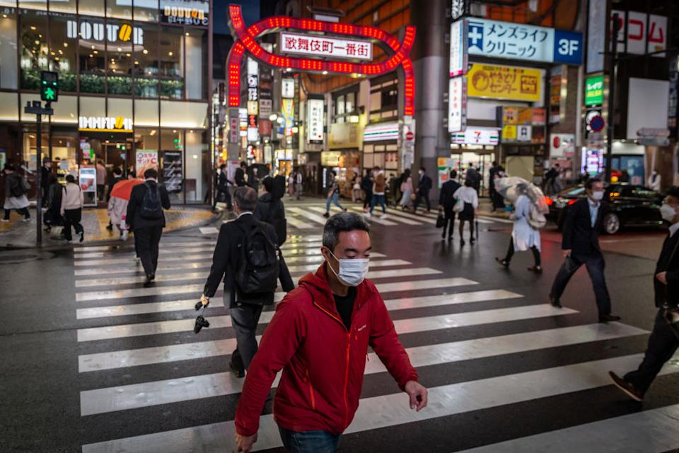 A man wearing a face mask crosses a road in Shinjuku area in Tokyo, Japan.