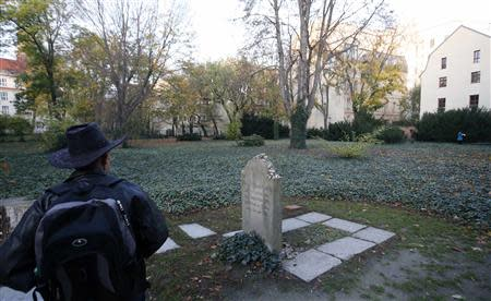 A visitor stands next to gravestone of German philosopher Mendelssohn at Jewish cemetery in Berlin