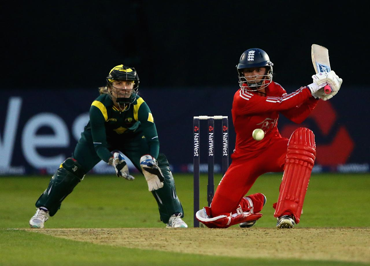 CHELMSFORD, ENGLAND - AUGUST 27:  Danielle Wyatt of England plays a shot as Jodie Fields of Australia keeps wicket during the 1st NatWest T20 match between England Women and Australia Womens at Ford County Ground on August 27, 2013 in Chelmsford, England.  (Photo by Julian Finney/Getty Images)