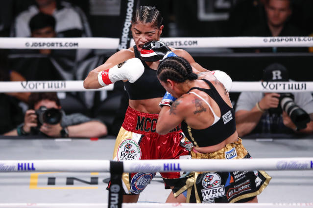 Erica Farias, right, hits Jessica McCaskill during a super lightweight boxing bout Saturday, Oct. 12, 2019, in Chicago. (AP Photo/Kamil Krzaczynski)