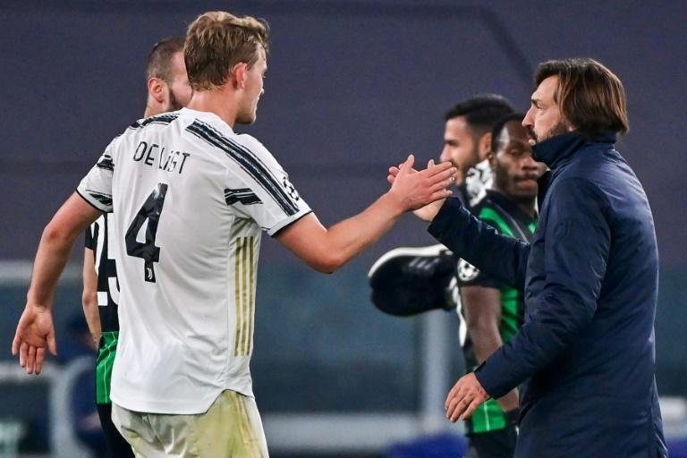 Juventus' Italian coach Andrea Pirlo (R) taps hands with Dutch defender Matthijs De Ligt.