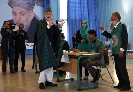 Afghan President Hamid Karzai shows his card before voting in the presidential election in Kabul