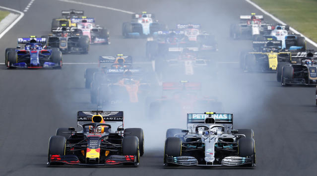 Red Bull driver Max Verstappen, left, of the Netherlands, and Mercedes driver Valtteri Bottas, of Finland, lead the field during the Hungarian Formula One Grand Prix at the Hungaroring racetrack in Mogyorod, northeast of Budapest, Hungary, Sunday, Aug. 4, 2019. (AP Photo/Laszlo Balogh)
