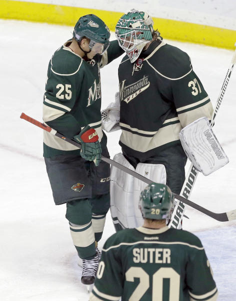 Minnesota Wild goalie Josh Harding, top right, is congratulated by teammate Jonas Brodin, left, as Wild's Ryan Suter , bottom, looks on after they defeated the Winnipeg Jets 2-1 in an NHL hockey game on Thursday, Oct. 10, 2013, in St. Paul, Minn. It was their first win of the season. (AP Photo/Jim Mone)