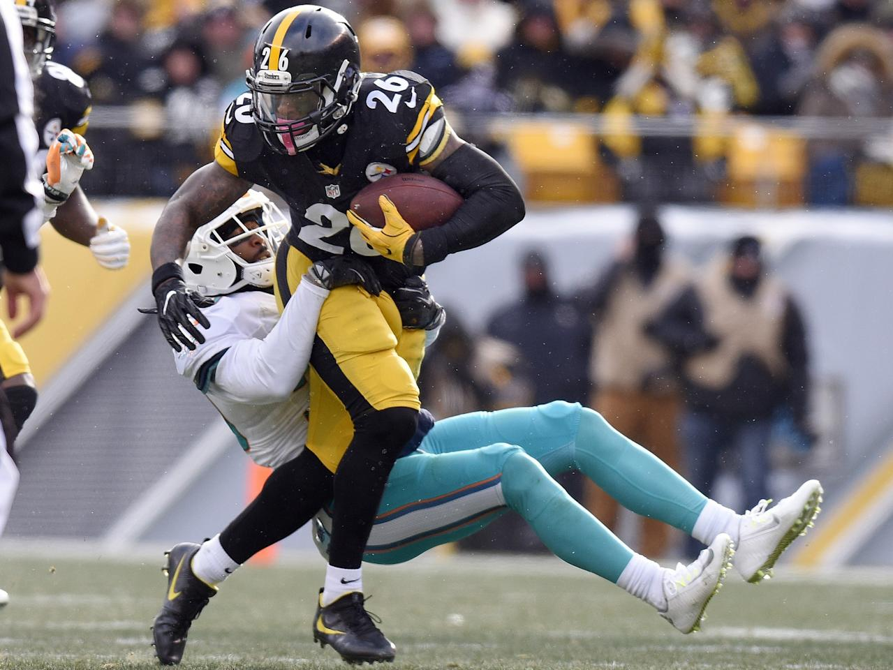 <p>Pittsburgh Steelers running back Le'Veon Bell (26) runs through a tackle by Miami Dolphins free safety Bacarri Rambo during the first half of an AFC wild-card in Pittsburgh, Jan. 8, 2017. Bell has rewritten the record books once again, breaking the franchise's single-game postseason rushing mark in Sunday's 30-12 AFC wild-card victory. (Photo: Don Wright/AP) </p>