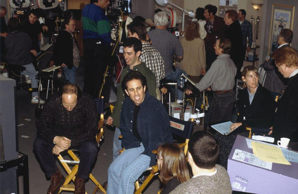 """<p>Seinfeld is seen sitting behind the monitor while a scene is taped. As the star and co-creator, Seinfeld was viewed as the <a href=""""https://www.forbes.com/sites/robasghar/2014/06/29/the-three-key-leadership-lessons-from-seinfeld/#697ad3ce269b"""" rel=""""nofollow noopener"""" target=""""_blank"""" data-ylk=""""slk:show's fearless leader"""" class=""""link rapid-noclick-resp"""">show's fearless leader</a>. </p>"""