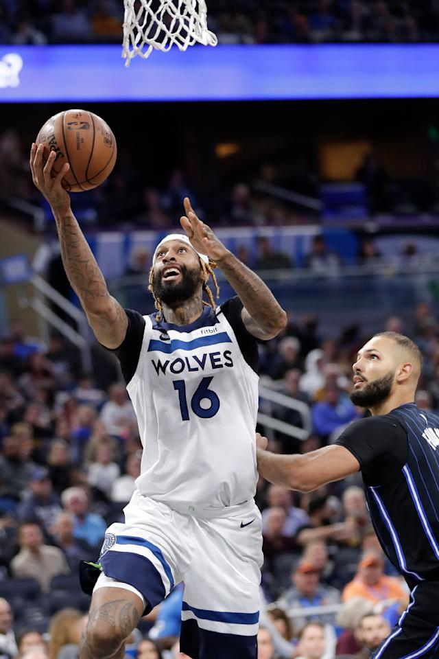 Minnesota Timberwolves forward James Johnson (16) makes a shot as he gets around Orlando Magic guard Evan Fournier during the first half of an NBA basketball game Friday, Feb. 28, 2020, in Orlando, Fla. (AP Photo/John Raoux)