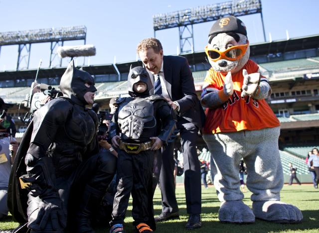 SAN FRANCISCO, CA - NOVEMBER 15: Larry Baer, CEO of the San Francisco Giants, and the team's mascot Lou Seal escort leukemia survivor Miles, 5, dressed as BatKid, and Batman to the outfield to see a message on the scoreboard as part of a Make-A-Wish foundation fulfillment at AT&T Park November 15, 2013 in San Francisco. The Make-A-Wish Greater Bay Area foundation turned the city into Gotham City for Miles by creating a day-long event bringing his wish to be BatKid to life. (Photo by Ramin Talaie/Getty Images)