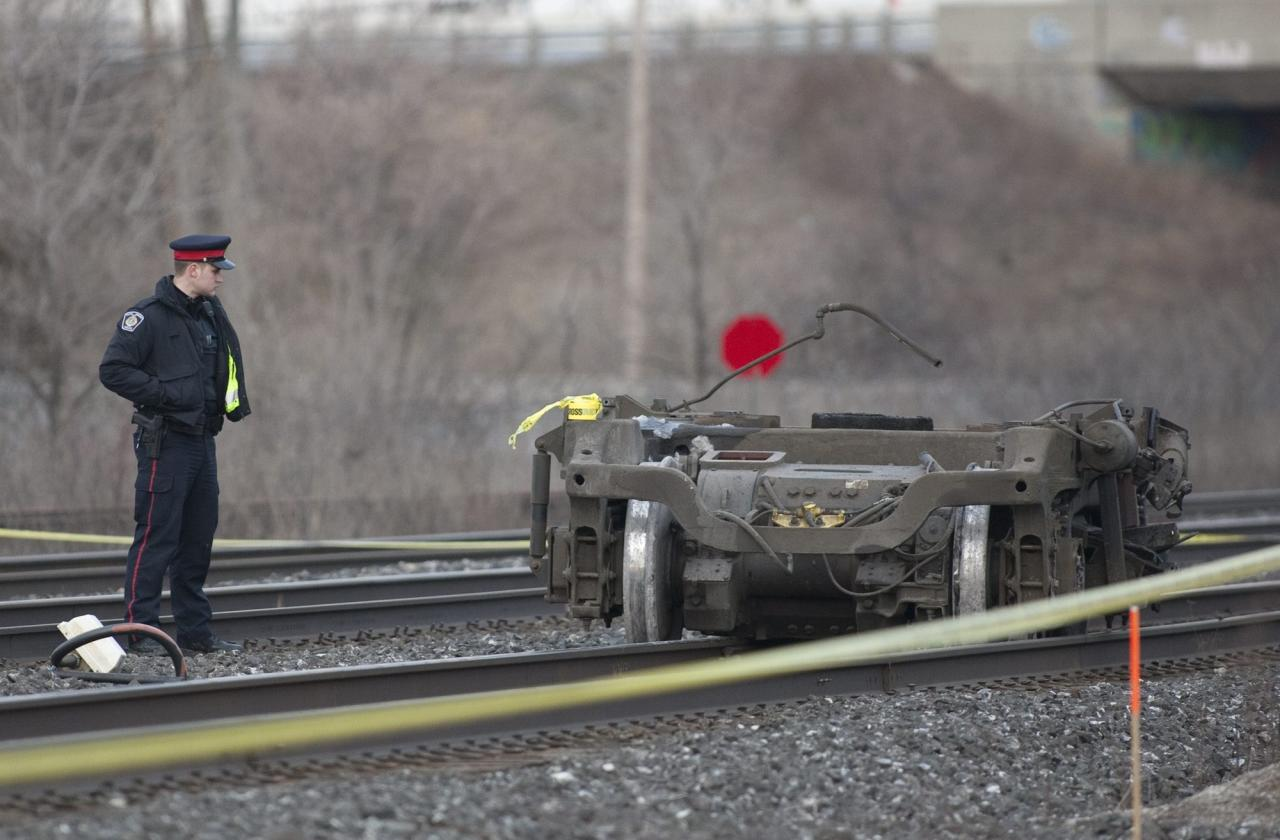 A police officer stands beside a piece of train wheels that fell off a Via Rail passenger train in Burlington, Ontario on Sunday, Feb. 26, 2012. Burlington Mayor Rick Goldring says three people are dead after the Toronto-bound train derailed in his town. (AP Photo/The Canadian Press, Pawel Dwulit)