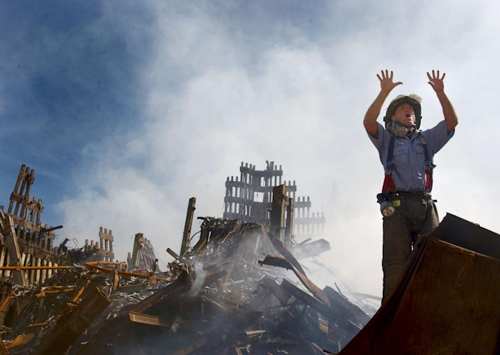 """A New York City fireman calls for ten more rescue workers to make their way into the rubble in this evocative photograph by U.S. Navy Photographer's Mate 1st Class Preston Keres. In the months and years since 9/11, the word """"heroes"""" has been tossed around so much that, in some respects, it's been made meaningless. But no sensible human being would argue that the work performed at Ground Zero by countless first responders -- police, EMTs, firefighters, and unheralded, anonymous volunteers who scrambled on to """"the pile"""" seeking survivors -- was anything less than heroic. It's an observation made a thousand times before, and yet it still bears repeating: as hundreds of thousands of panicked New Yorkers and tourists fled to safety and shelter, running away from the devastation, first responders were racing into the unimaginable slaughter and destruction. This photo -- and its call for """"ten more"""" -- remains a distilled reminder of their bravery and sacrifice. <br><br>(Photo: U.S. Navy Photo by Journalist 1st Class Preston Keres)<br><br>For the full photo collection, go to <a href=""""http://www.life.com/gallery/59971/911-the-25-most-powerful-photos#index/0"""" rel=""""nofollow noopener"""" target=""""_blank"""" data-ylk=""""slk:LIFE.com"""" class=""""link rapid-noclick-resp"""">LIFE.com</a>"""
