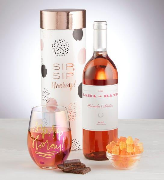 """<h2>Sip Sip Hooray Rosé Wine & Glass Gift Set</h2><br>This wine basket is filled with all Rosè-themed sweets like gummy bears and chocolate, and of course a full bottle. It also comes with a cute iridescent stemless glass for all your sipping. <br><br><strong><em>Shop 1-800 Flowers</em></strong><br><br><strong>1800 Flowers</strong> Sip Sip Hooray Rosé Wine & Glass Gift Set, $, available at <a href=""""https://go.skimresources.com/?id=30283X879131&url=https%3A%2F%2Fwww.1800flowers.com%2Fsip-sip-hooray-rose-wine-and-glass-gift-set-171898"""" rel=""""nofollow noopener"""" target=""""_blank"""" data-ylk=""""slk:1800 Flowers"""" class=""""link rapid-noclick-resp"""">1800 Flowers</a>"""