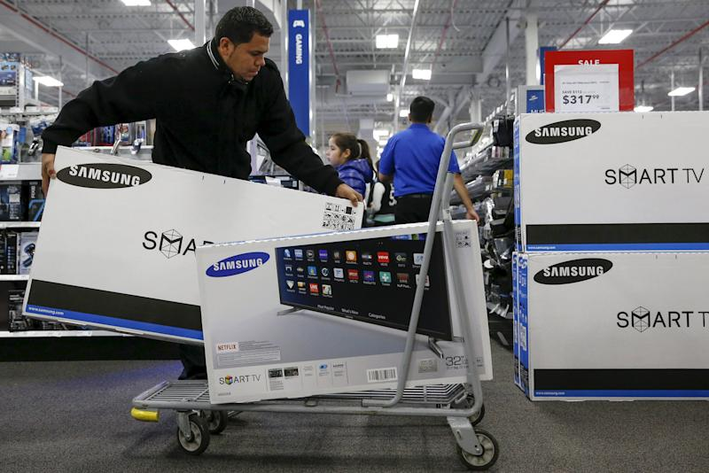 A shopper puts televisions on a shopping cart  at a Best Buy store in Westbury, New York November 27, 2015. Crowds were thin at U.S. stores and shopping malls in the early hours of Friday, initial spot checks showed, as shoppers responded to early Black Friday discounts with a mix of enthusiasm and caution. REUTERS/Shannon Stapleton