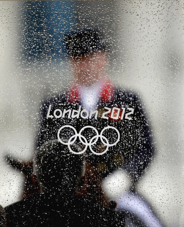 Rains drops collect on the window of a judge's booth as Richard Davison, of Great Britain, rides his horse Artemis, in the equestrian dressage competition at the 2012 Summer Olympics, Friday, Aug. 3, 2012, in London. (AP Photo/David Goldman)
