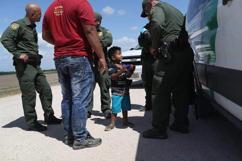 A boy and father from Honduras are taken into custody by U.S. Border Patrol agents near the U.S.-Mexico Border on June 12, 2018, near Mission, Texas. The asylum-seekers were then sent to a U.S. Customs and Border Protection (CBP) processing center for possible separation.