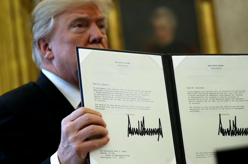 U.S. President Donald Trump holds up a copy of legislation he signed before before signing the tax reform bill into law in the Oval Office December 22, 2017 in Washington, DC. (Photo: Chip Somodevilla/Getty Images)