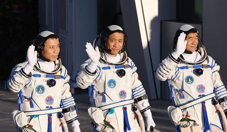 The astronauts (from left) Tang Hongbo, Nie Haisheng and Liu Boming wave before boarding their spacecraft on June 17. Photo: AFP