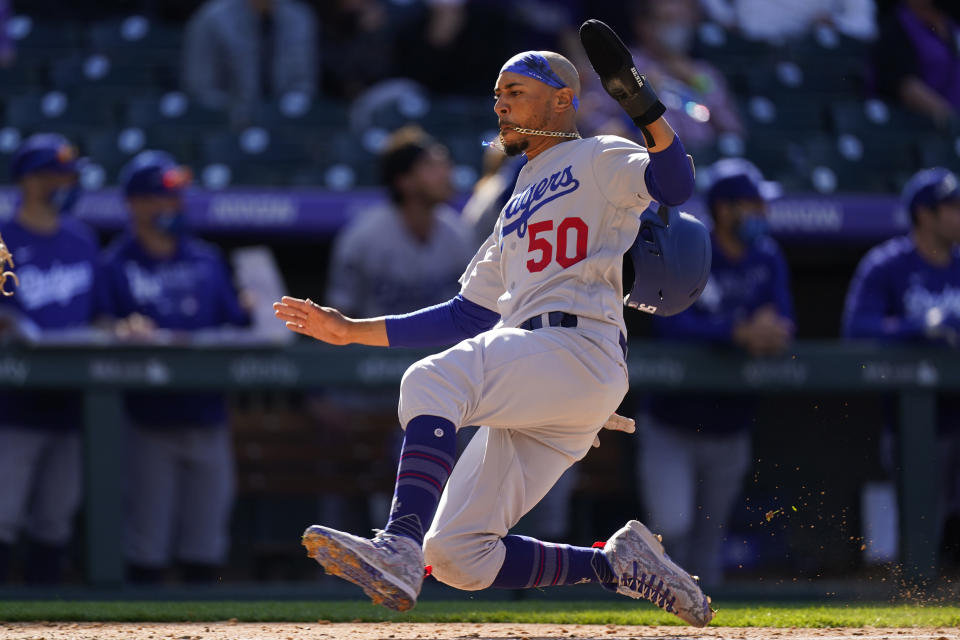 Los Angeles Dodgers' Mookie Betts slides across home plate to score on a single by Max Muncy off Colorado Rockies relief pitcher Chi Chi Gonzalez in the sixth inning of a baseball game Thursday, April 1, 2021, in Denver. (AP Photo/David Zalubowski)