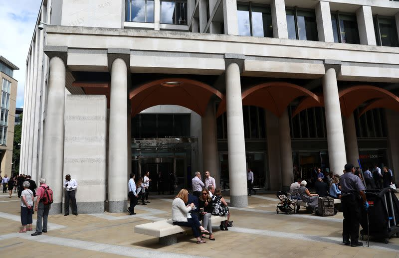 People stand and sit outside the London Stock Exchange in Paternoster Square, London