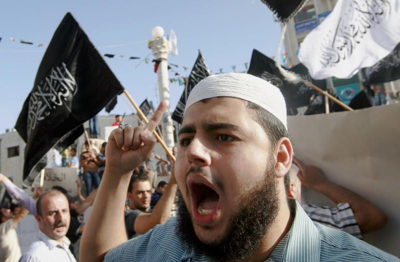 """Palestinian supporters of Hizbut-Tahrir, or Party of Liberation, shout slogans during a rally in the West Bank city of Ramallah, Tuesday, June 4, 2013. Arabic words on the flags read: """"There is no god but God, and Mohammed is his prophet."""" A senior Palestinian official says the West Bank government will try to bring Israel up on charges through the U.N. if American attempts to restart peace talks fail. (AP Photo/Majdi Mohammed)"""