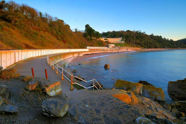 Looking along the promenade of Meadfoot Beach in Torquay in South Devon England at sunrise